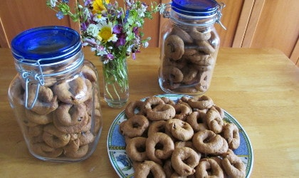 Olive oil orange juice cookies on a plate and in two large jars near a glass of wildflowers