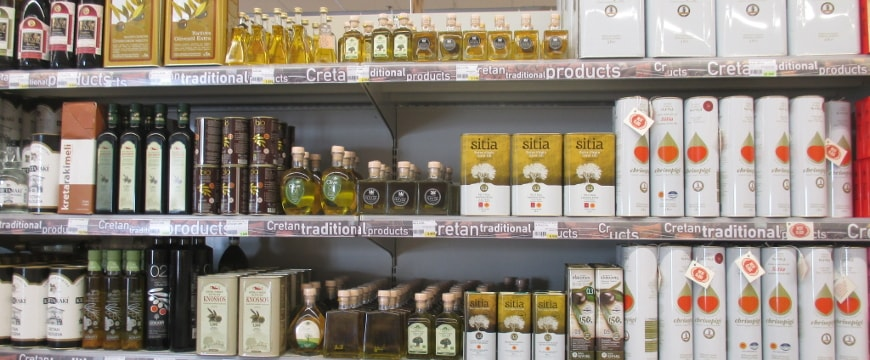 A variety of olive oil bottles on the shelves of a Greek supermarket