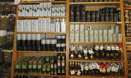 Bottles and tins of olive oil on store shelves