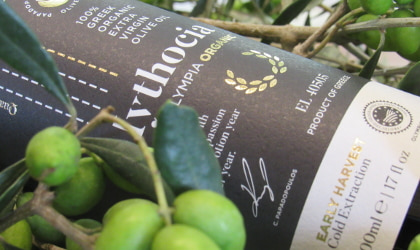 part of a bottle of the Papadopoulos Olive Oil company's Mythocia olive oil lying on its side next to green olives