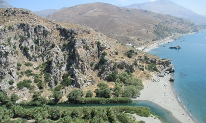 View of river, palm trees, beach, sea, and hills at Preveli, Crete