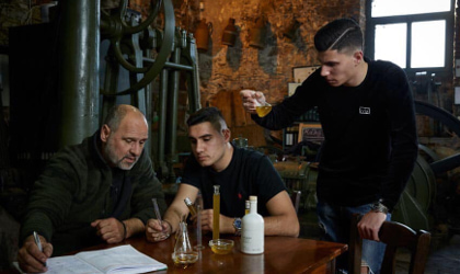 Kostas Protoulis and his two sons examining olive oil at a table