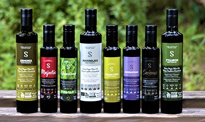 Bottles of Sakellaropoulos Organic Farming olive oils lined up in a row