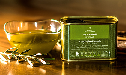 a rectangular tin of Fyllikon olive oil next to a glass bowl of olive oil, with an olive branch in front of it