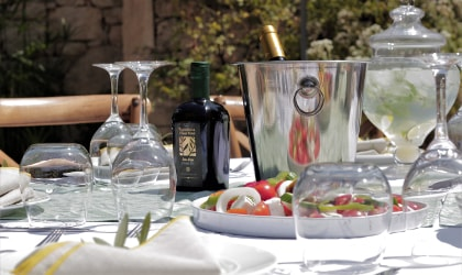 A table with olive oil, salad, glassware, and dishes (viewed from the side)