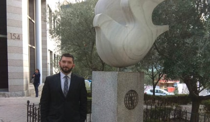Vasilis Pyrgiotis standing next to International Olive Council symbols, a globe with an olive branch under a sculpture of a bird