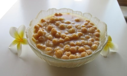 chickpeas in a glass bowl with yellow and white plumeria flowers next to it