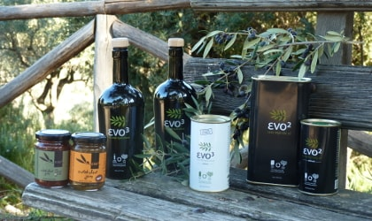 evo3 bottles, jars, and tins of olive oil and related products on a wooden bench outdoors