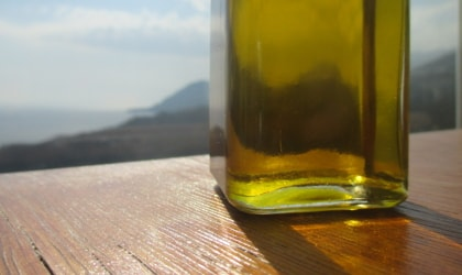 the bottom of a clear bottle of olive oil on a wooden tablel, with a sea view beyond it