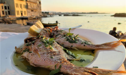 two whole fish on a plate of olive oil, with the sea in the background
