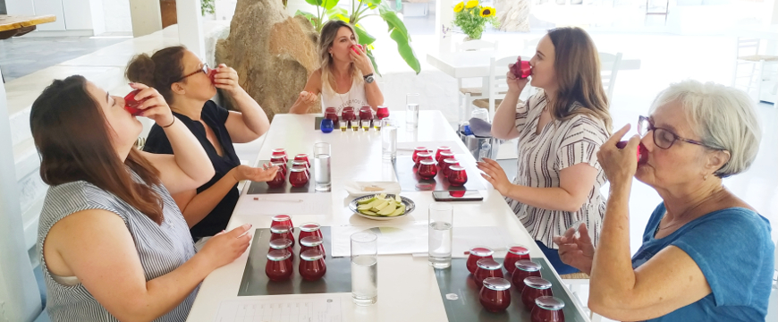 women sitting at a table, tasting olive oil from red tasting glasses