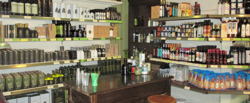 olive oils and other products on the shelves of a specialty store in Athens, with a small table for sampling products in front of the shelves