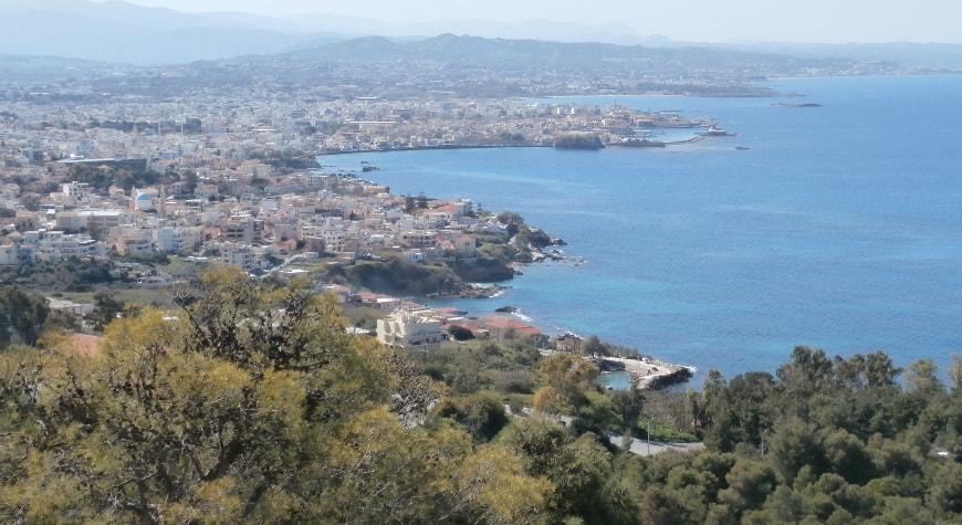 City of Chania viewed from a hill above it, with olive groves in front right and sea on the right