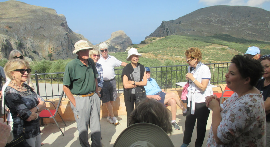 visitors learning about olive oil at Biolea, with hills and sky in the background