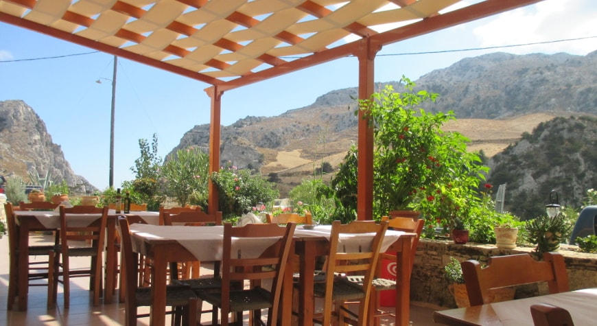 Tables, plants, and view of hills and sky at Iliomanolis Taverna