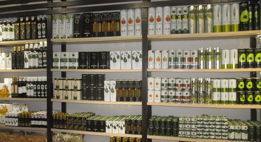 a variety of bottles and tins of Cretan olive oils on the shelves in the Kipsel shop in Sitia