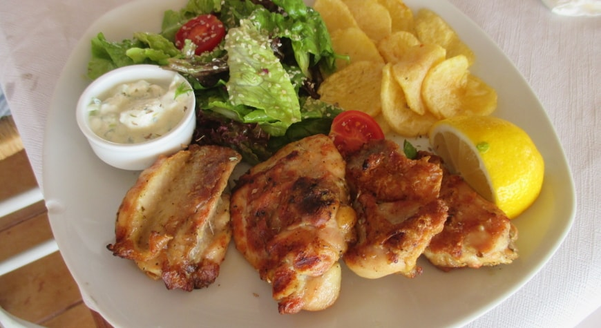 chicken thighs, fried potatoes, small salad, tzatziki, and lemon at Plateia Taverna