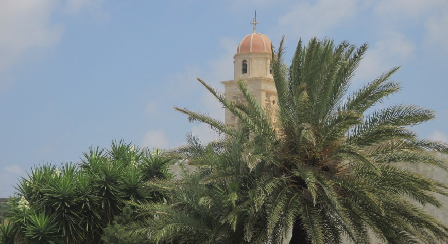 the belltower of the Toplou Monastery rishing above palm trees and yucca plants