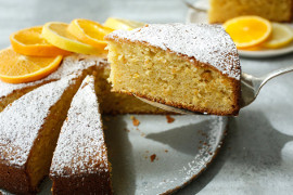 Almond cake, sliced in wedges and sprinkled with powdered sugar, with orange slices behind it