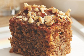 Chunk of dark brown cake with pieces of nuts on top and inside it