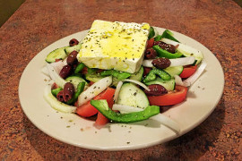 Greek salad with a large square of white feta cheese on top