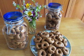 Olive oil orange juice cookies on a plate and in two glass jars near a glass of flowers