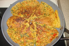 carrot onion parsley frittata in a frying pan