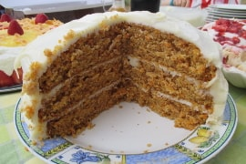 three layer carrot cake with cream cheese icing, with a big wedge cut out of it