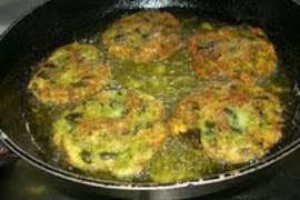 Zucchini patties frying in a cast iron skillet