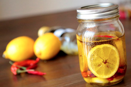 Jar containing olive oil with lemon slices and red chili peppers, with lemons and chili peppers on the table left of the jar