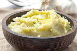 a dark bowl of mashed potatoes, with heads of garlic behind it